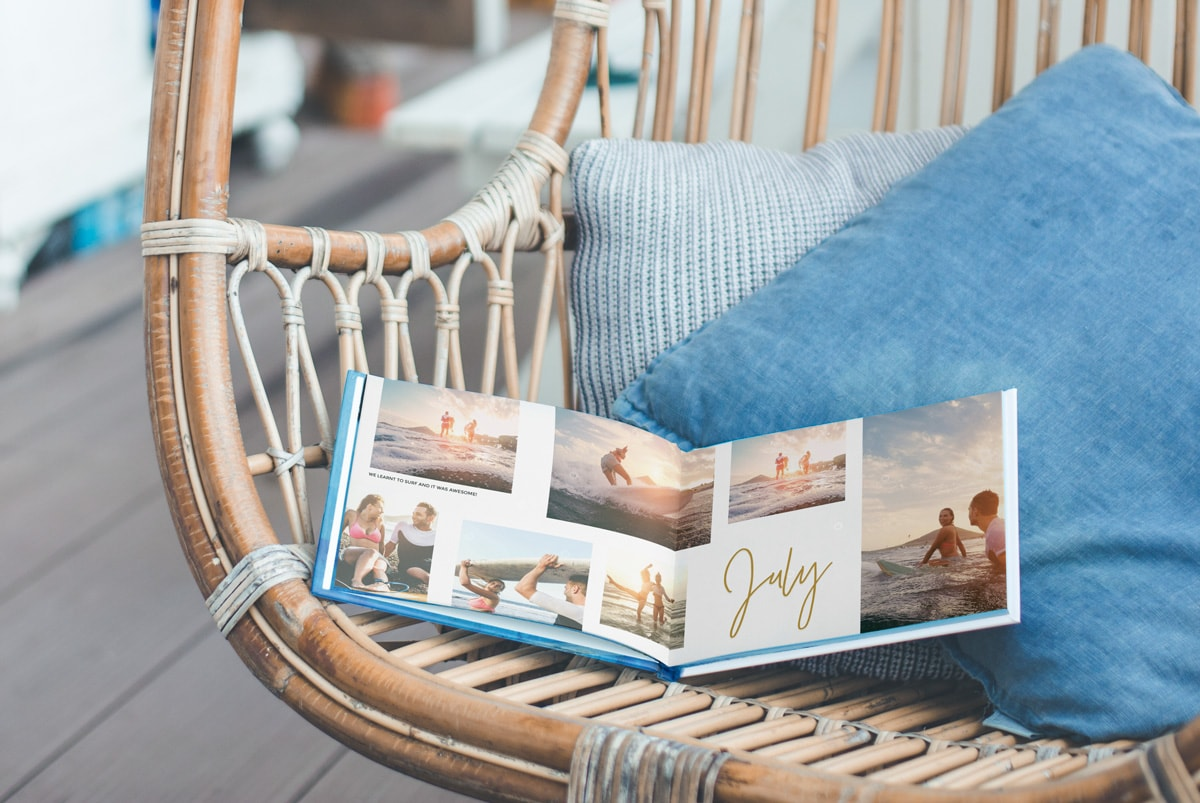 A photo book open on a chair outside with summery photos of people surfing in the book.