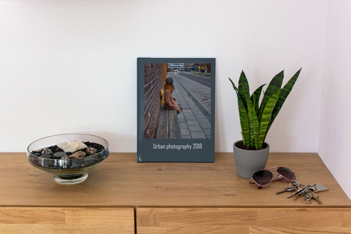 A portfolio of urban photography standing on a wooden side table.