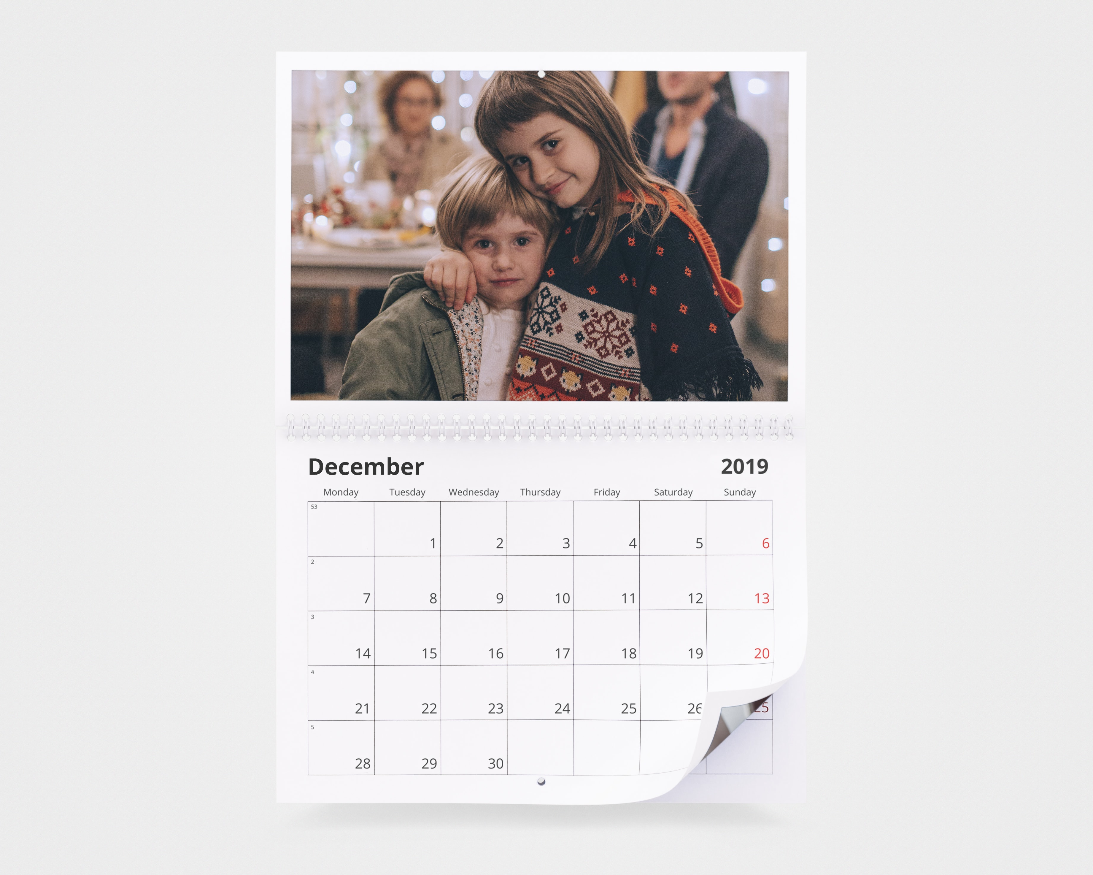 A photo calendar with an image of two children on in Christmassy jumpers and winter coats