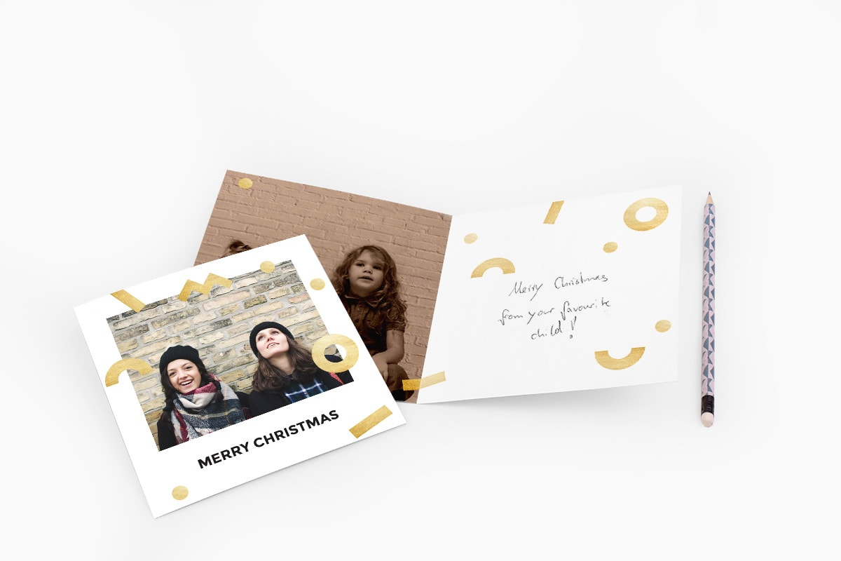 Black and white Christmas card with gold decoration and a photo of two sisters on the front