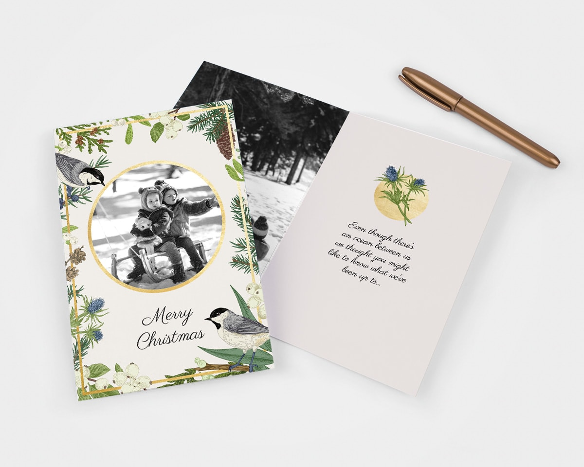 Traditional style Christmas card with wintery illustrations and a black and white photo on the front