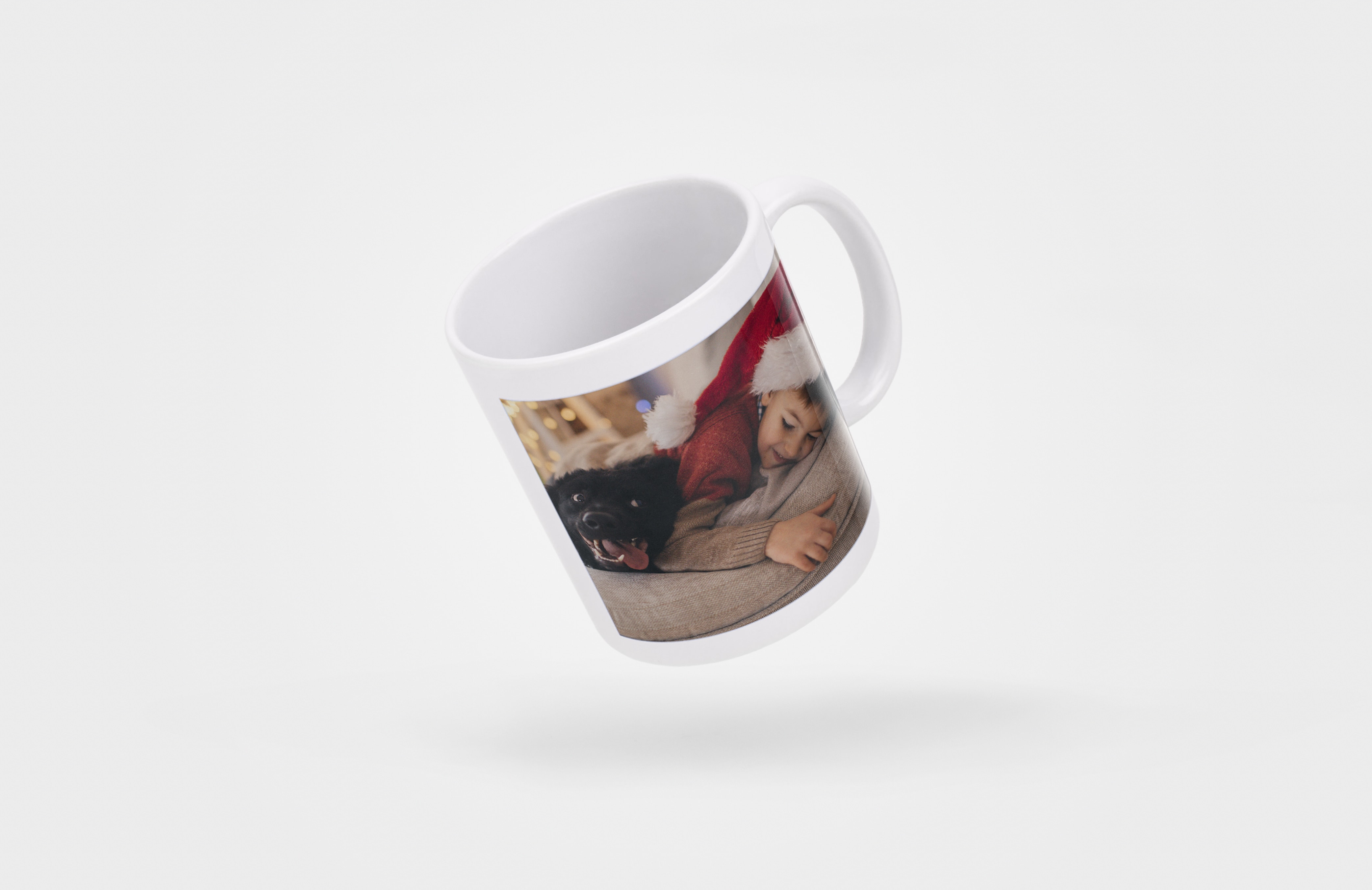 : A photo mug with an image of a little boy in a Santa hat lying on the sofa with his dog