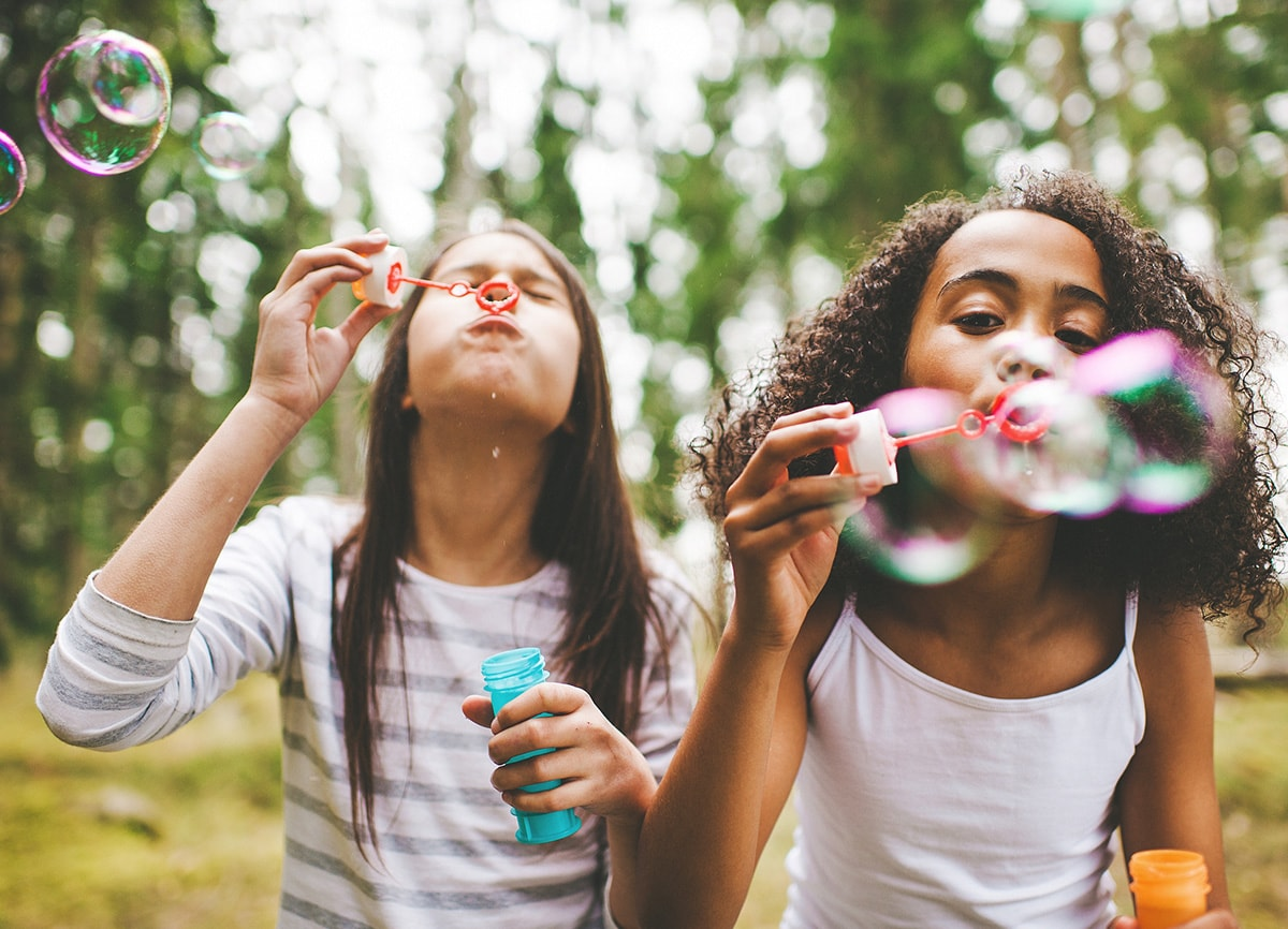 Two girls blowing bubbles outside. They are in focus, the background is out of focus.