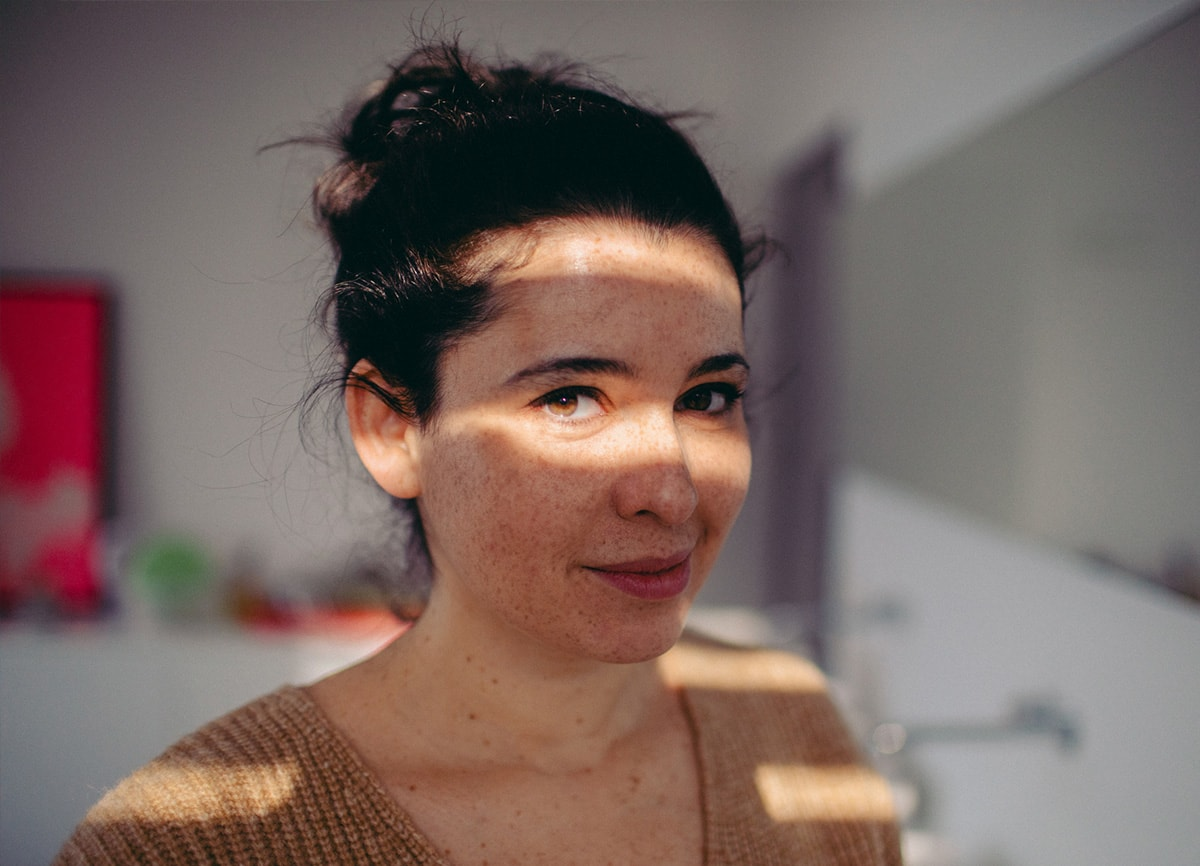 A woman standing in a room. Only some light is hitting her face through some blinds. She is in focus, the background is blurry.
