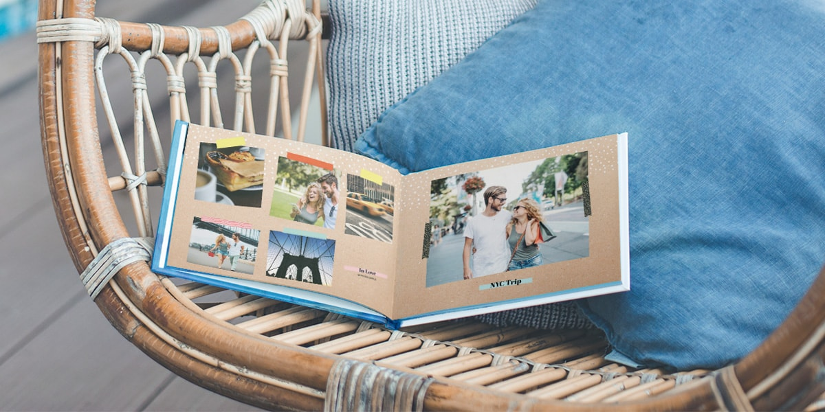 An open pre-designed photo book on a chair, with holiday pictures inside taken by a couple in New York