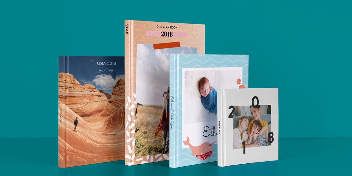 Four bonusprint yearbooks against a teal background, with travel pictures on two of the covers, one photo book with a baby on the cover and one with a family photo on the cover.