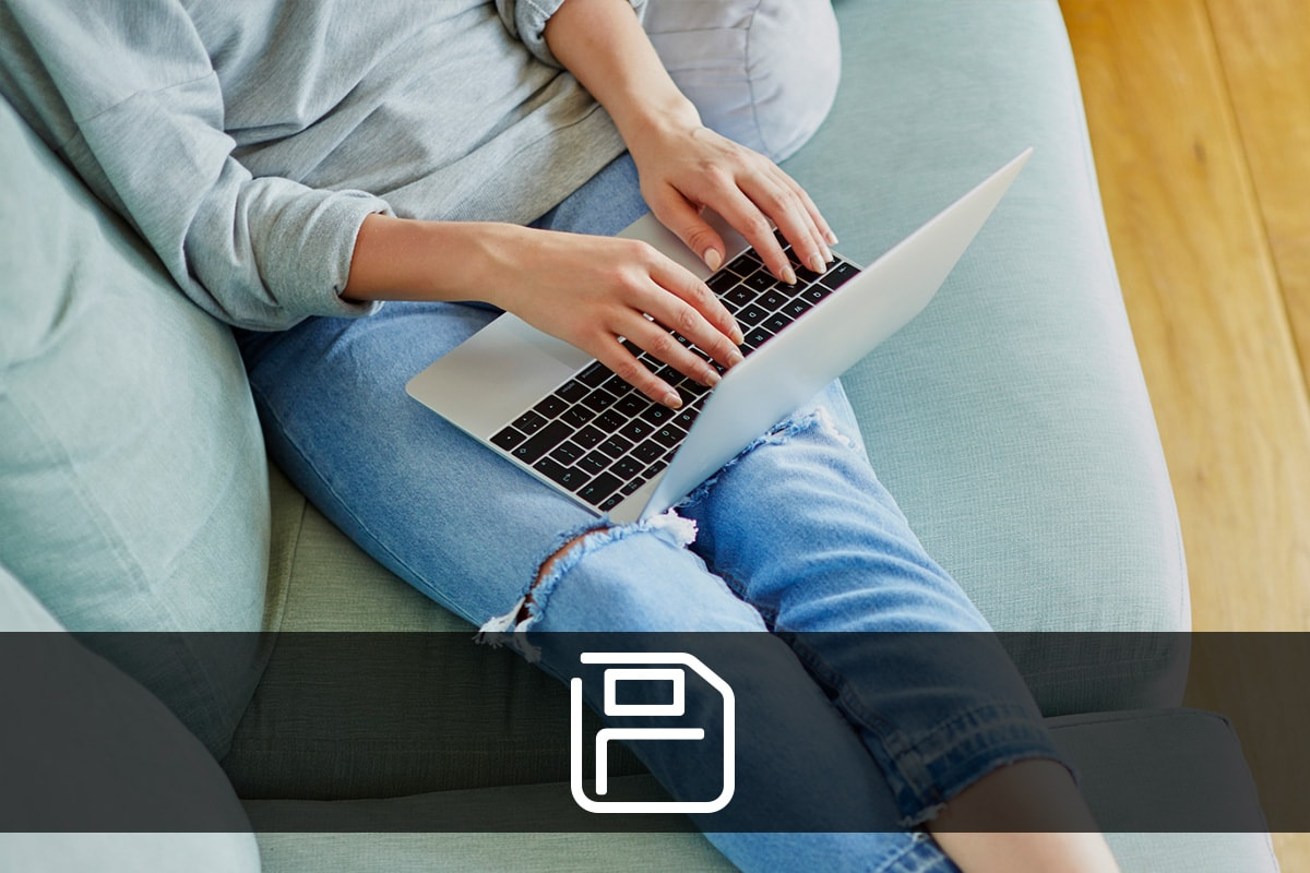 A woman wearing jeans and a grey jumper sat with her legs on a grey sofa with a laptop on her knee. There's a save icon on a black bar across the bottom of the image.