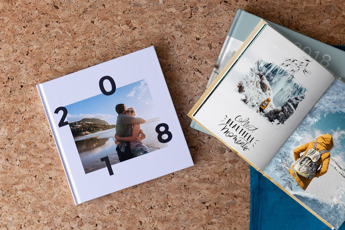 Three 2018 yearbooks on a cork table top. One book has two people hugging on the beach on the cover, another is open with a wintery photo mask over two images in the book.