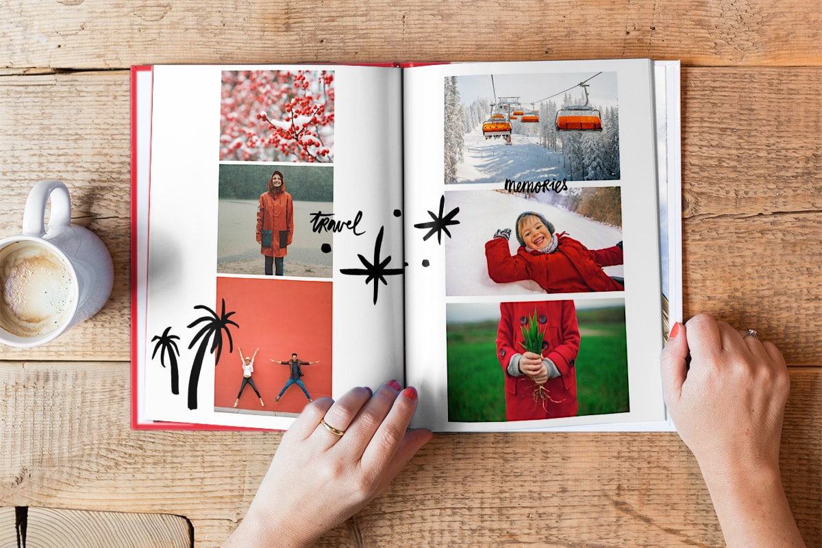 A photo book open on a wooden table top. All the images in the photo book have similar red tones in them, like a child wearing a red coat and a picture of red berries in the snow.