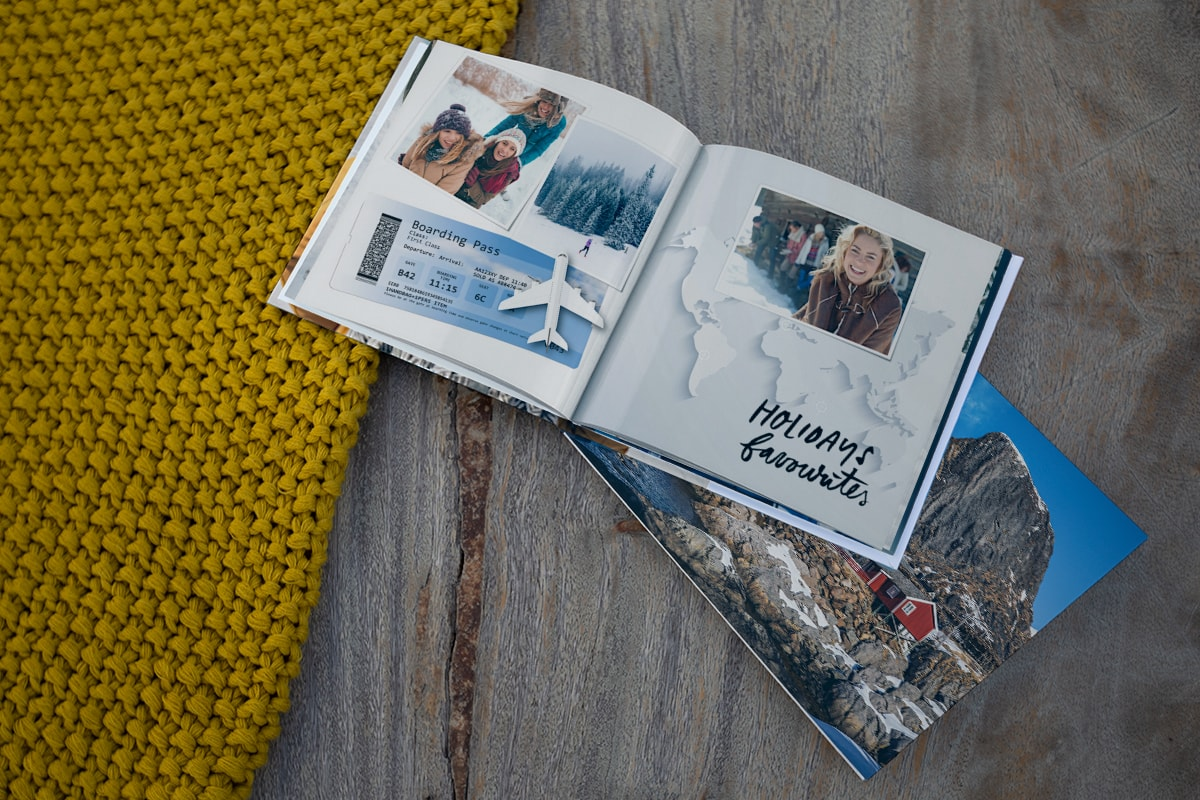 Two photo books on a wooden surface. One is open with family ski holiday pictures inside and a scanned boarding pass on the page.