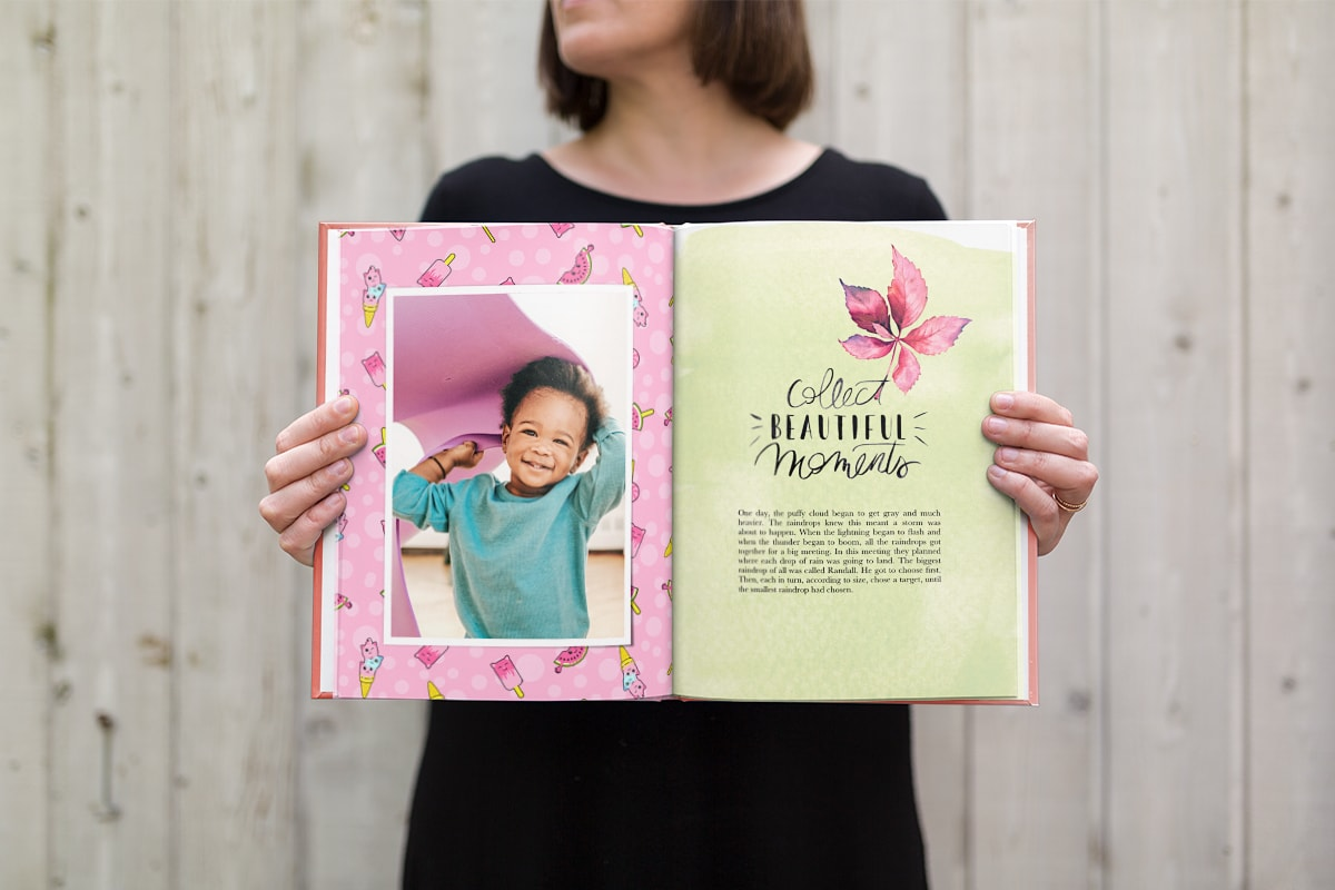 A woman holding a photo book open. There's an image of a baby smiling on one page of the book and a short paragraph of text on the opposite page.