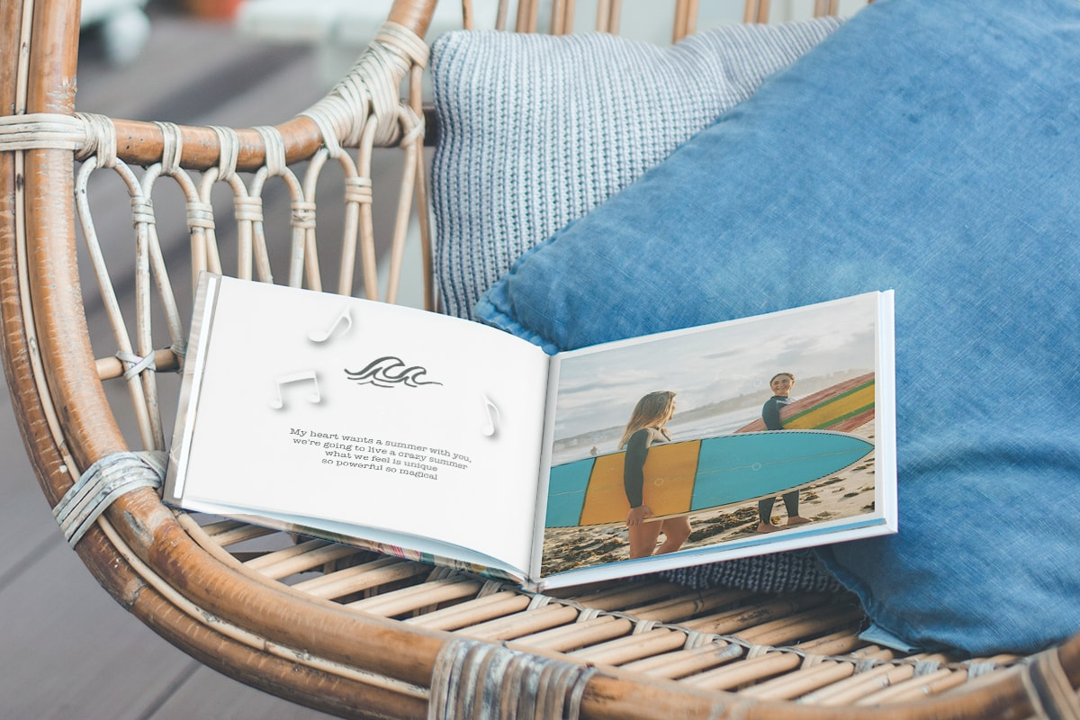 A photo book open on a wicker chair outside, with a surfing photo on one page and song lyrics on the left page with wave and music note illustrations on.