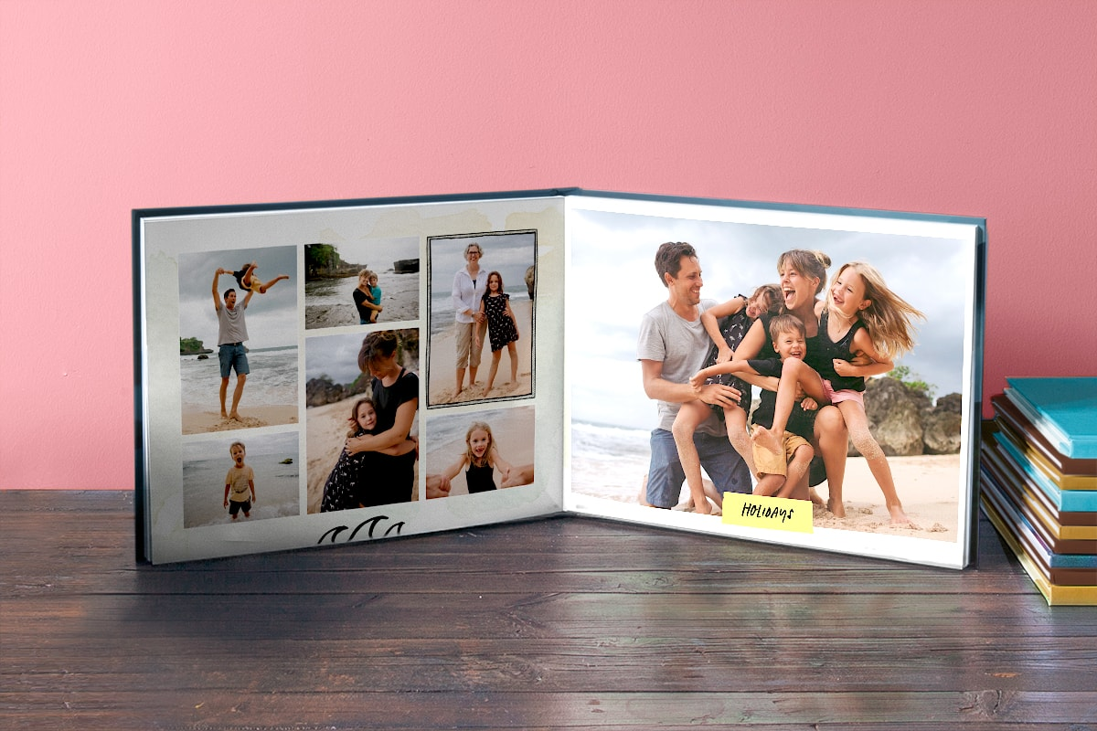 A photo book open against a pink background, with a grid of family holiday photos on the left page and a large family photo on the right page.
