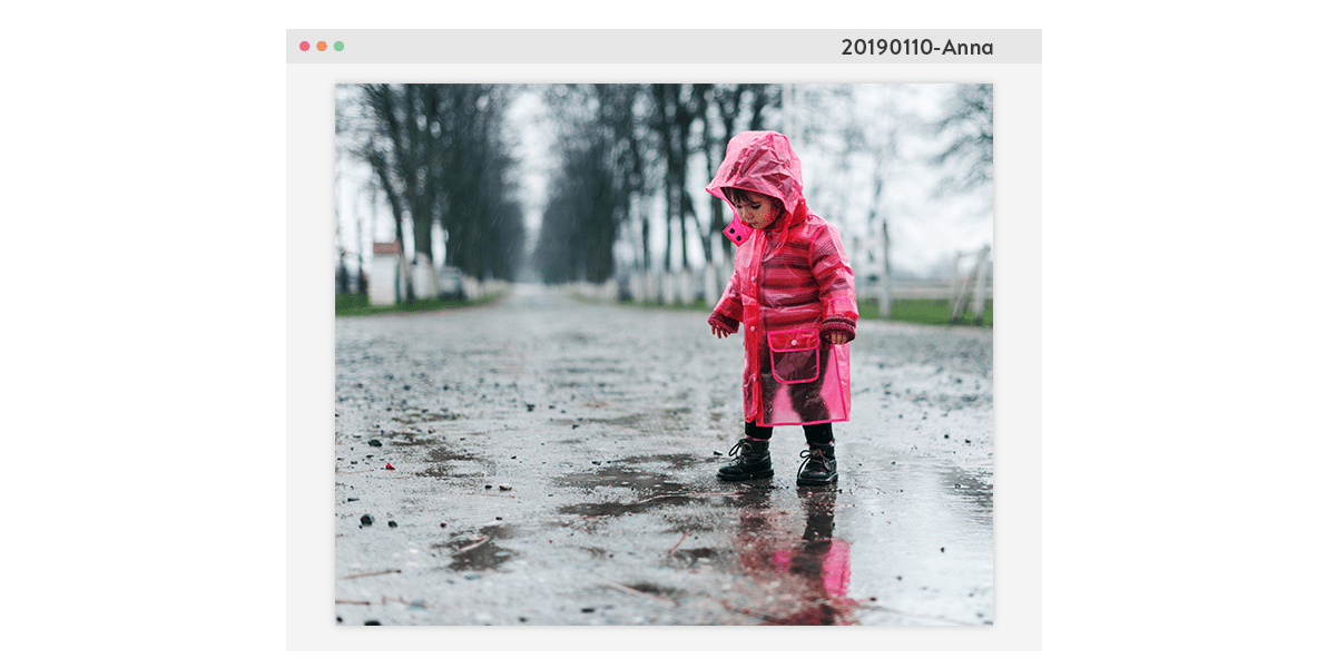A photo of a little girl in a pink raincoat stood on a rainy path. The picture is framed by a computer window with a file name in the top right corner.