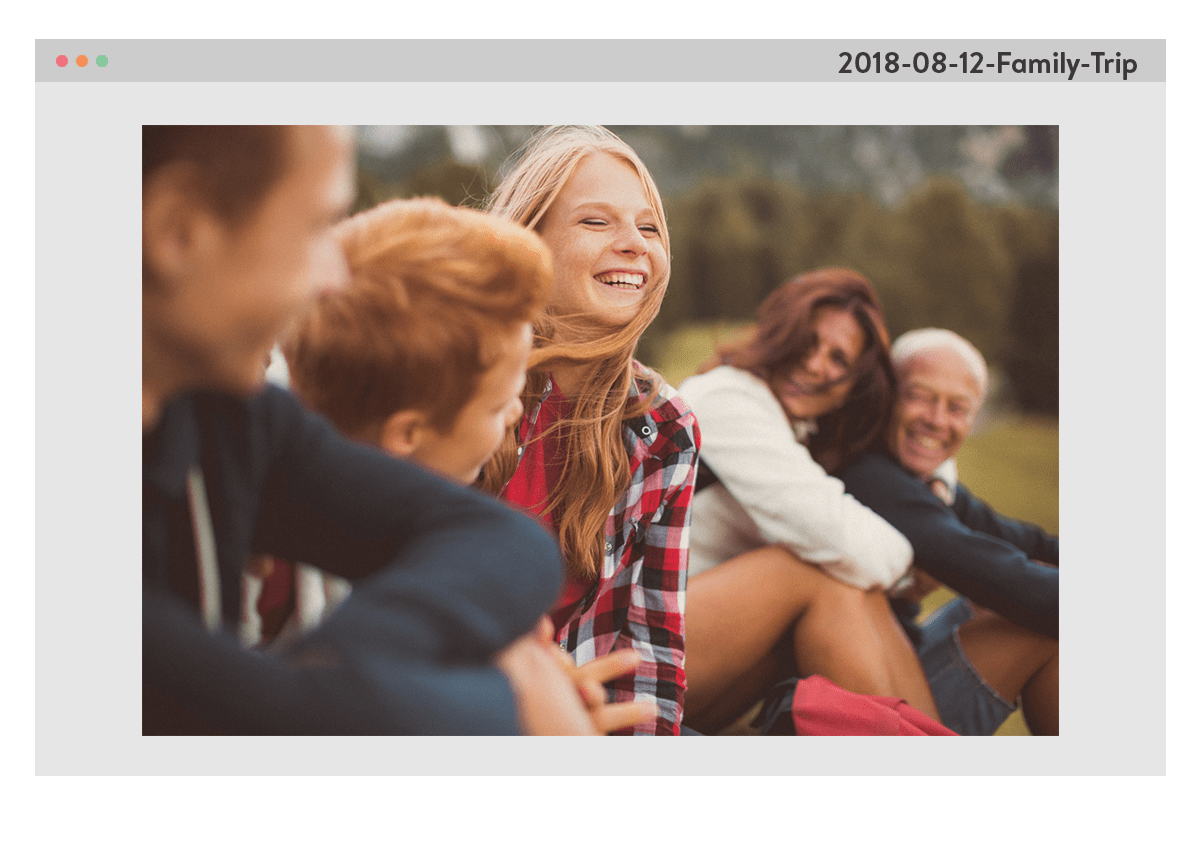 A photo of a family, sat outside on the grass, smiling. The photo is framed by a computer window, with the file name 2018-08-12-Family-Trip in the top right corner.
