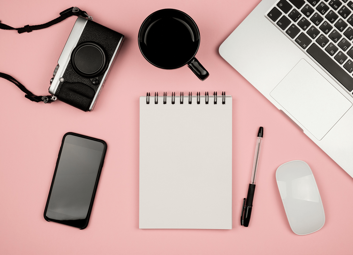 A topdown photo of a laptop, camera, notepad, pen, phone, computer mouse and a mug on a pale pink surface.