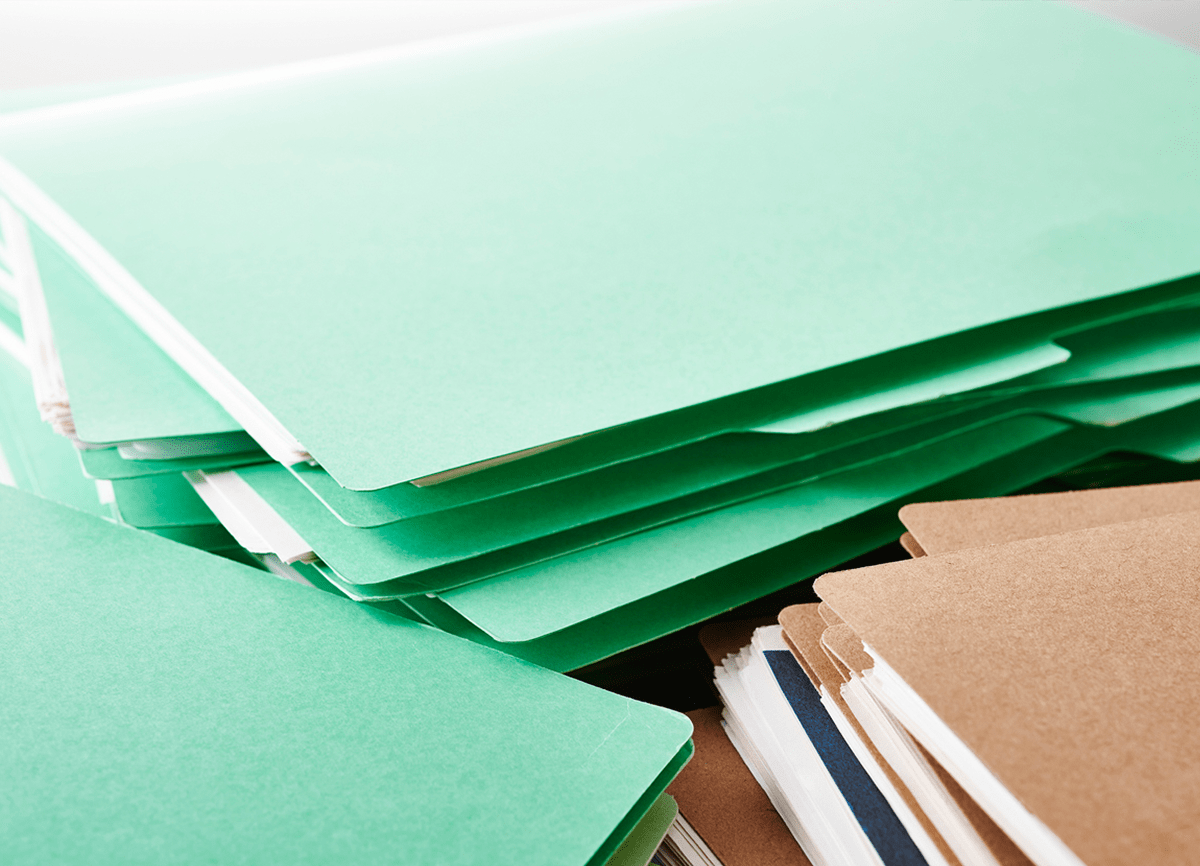 Three stacks of paper folders, two piles are green folders and the other stack is of brown folders.