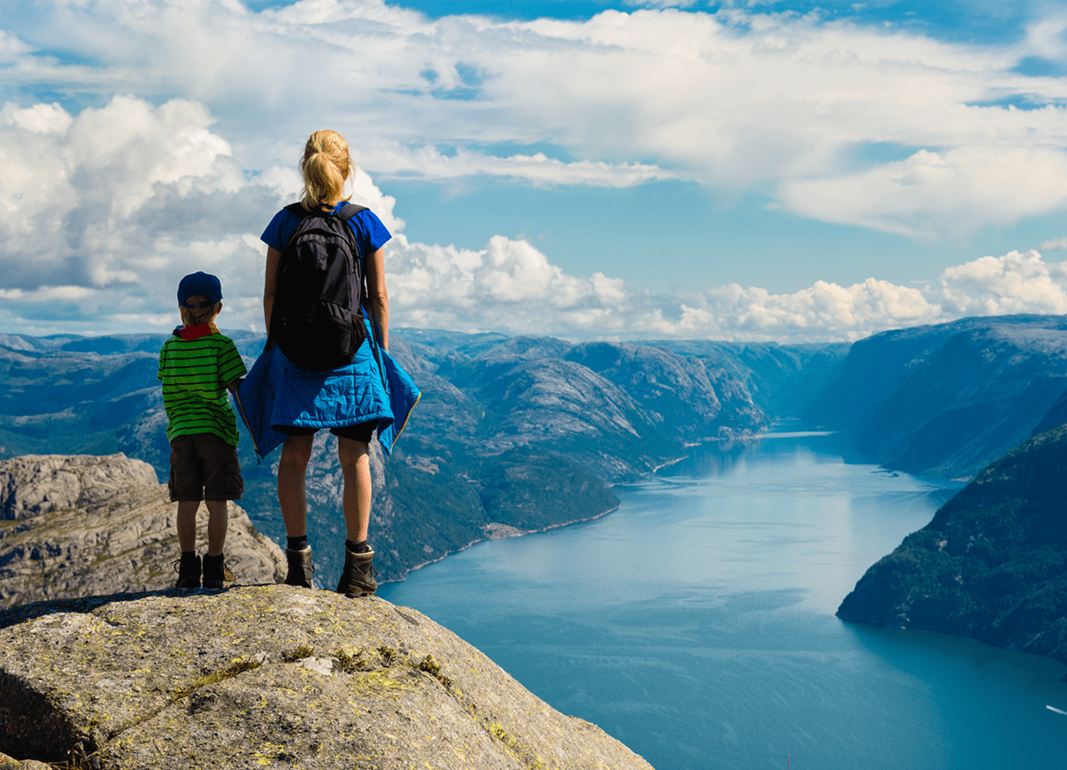 A woman and a young boy in hiking gear standing on a hill top with their backs to the camera, overlooking a river surrounded by mountains.