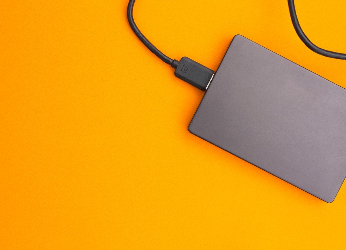 A topdown shot of a black external hard drive on a bright orange surface.
