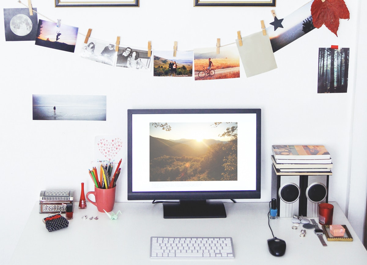A photo of a white desk in a white room, with a computer, speakers, keyboard, mouse, stationery and books on the desk, and a selection of photos clipped to a string hanging above it.