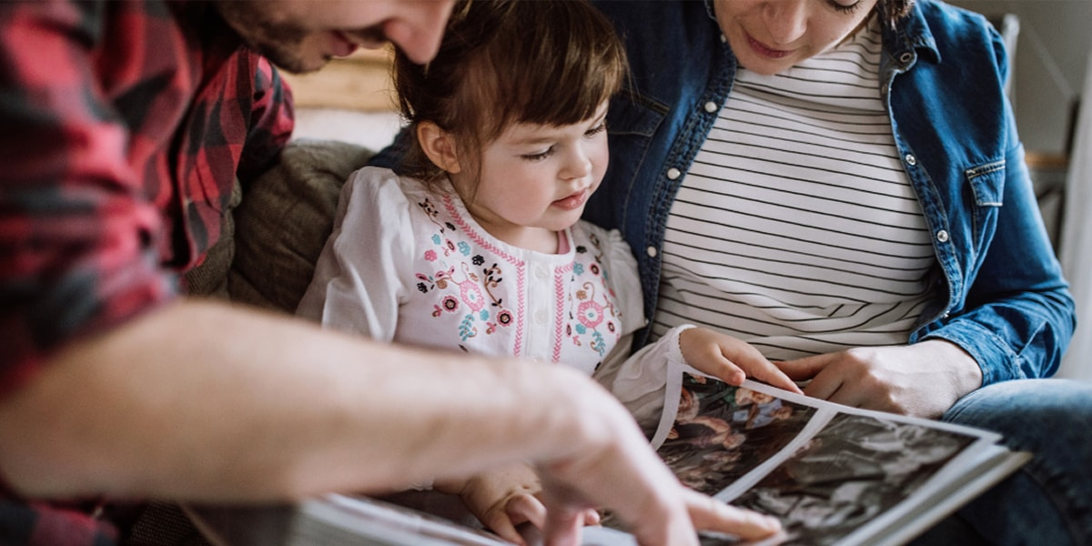 A man and a woman sitting with a little girl, flipping through a family photo book