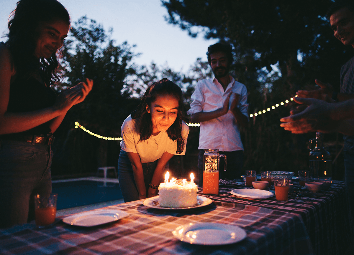 A girl blowing out candles on a birthday cake at a party outdoors at night.
