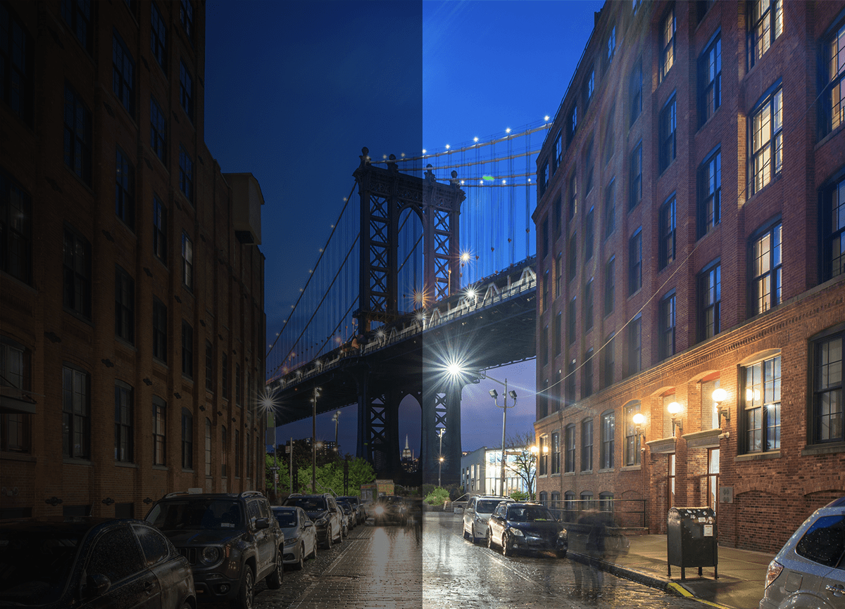 An image of a street at night with the Brooklyn Bridge at the end of the street. One half of the image is dark and barely visible, the other half is brighter and the people in it are blurred.