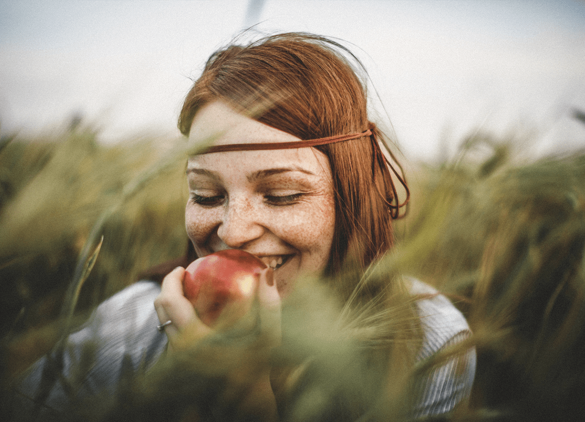 A girl eating an apple in a field of long grass. Grass in the foreground and background is blurred slightly, but the girl is in focus.