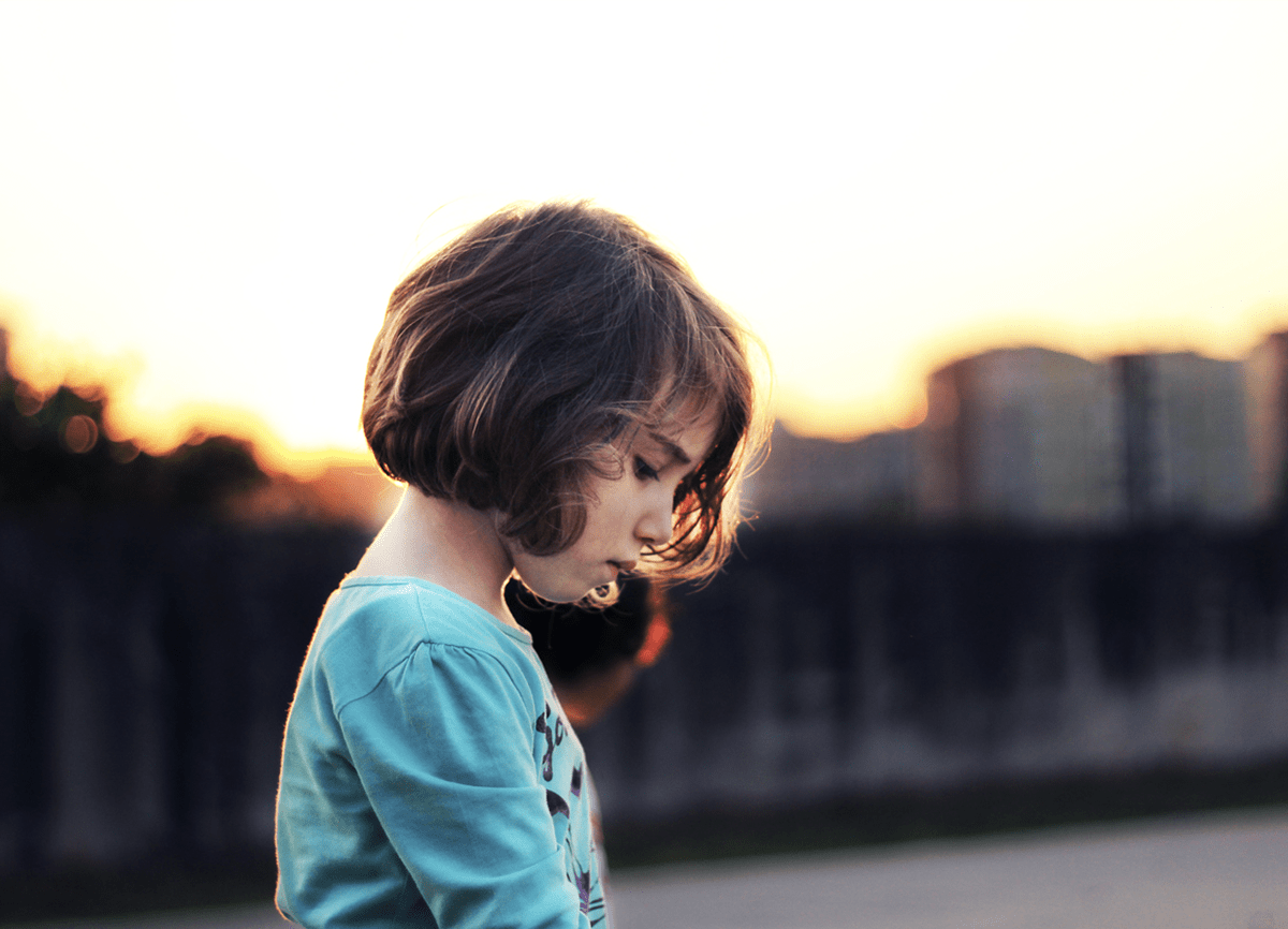 A little girl stood outside at sunset. The buildings in the background are blurred, but the girl is in focus.