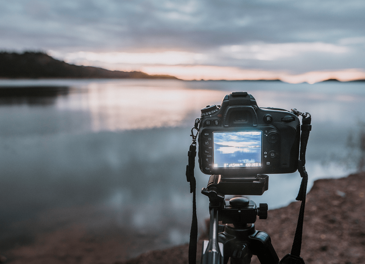 A DSLR camera on a tripod pointed at a lake in low light. The camera is in focus, the background is blurred.