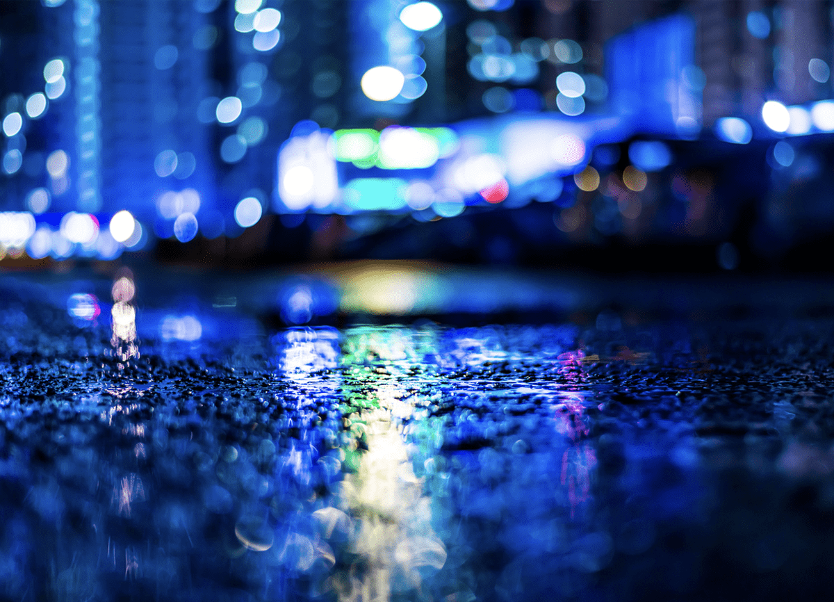 A photo taken very low to the ground on a rainy night. There are bright lights in the background that are out of focus.