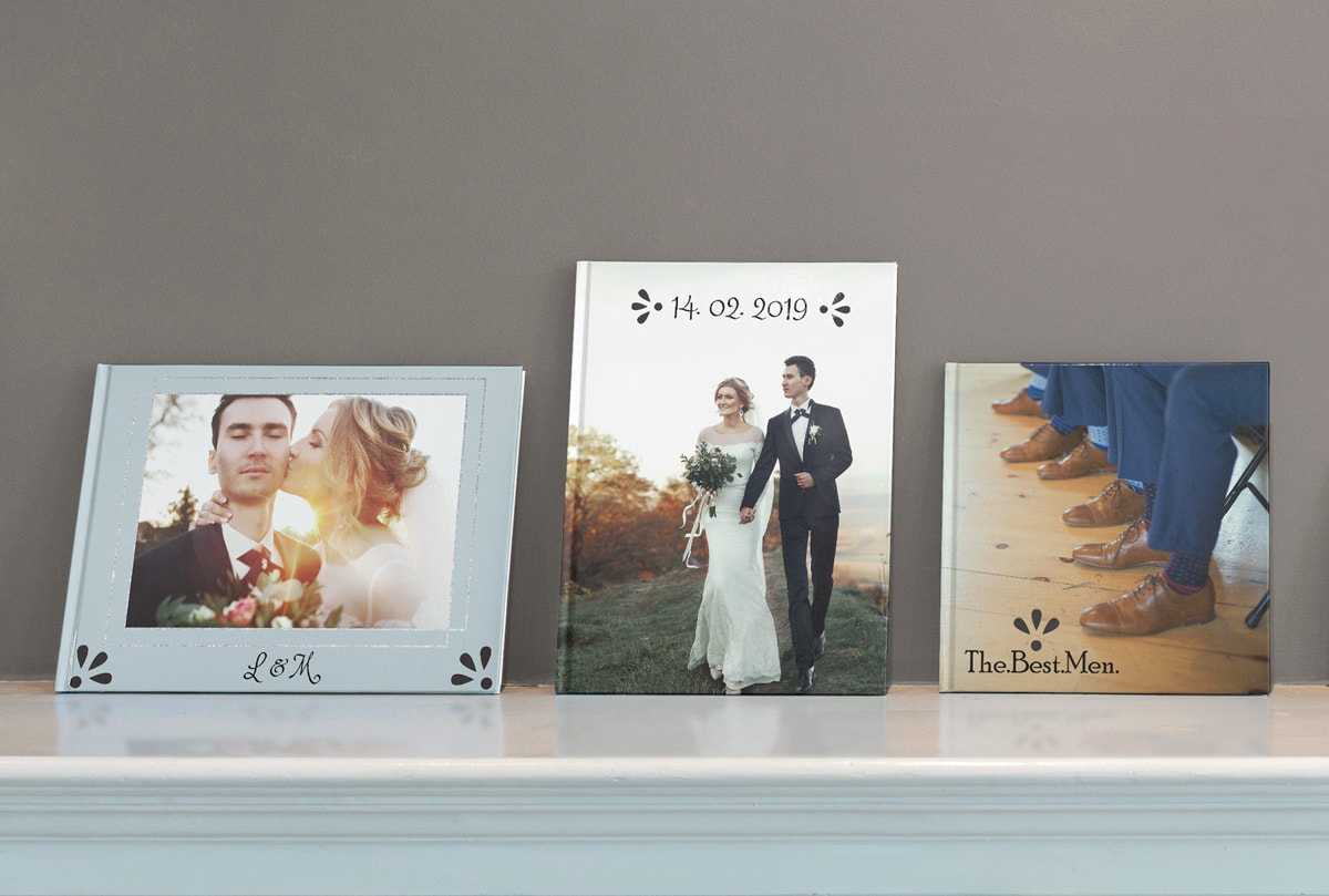 Three customised wedding photo books propped up against a wall, including a landscape, portrait and a square option.