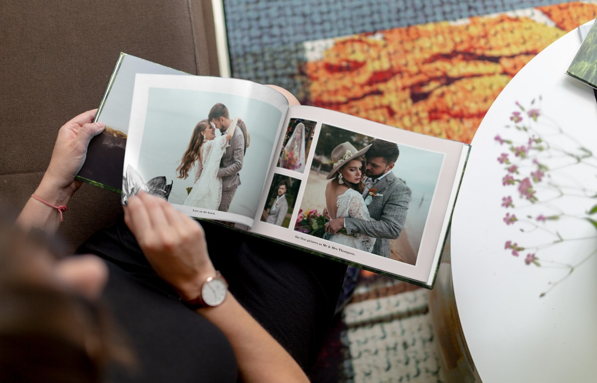 A photo of a woman sitting down flipping through a pre-designed wedding photo album.