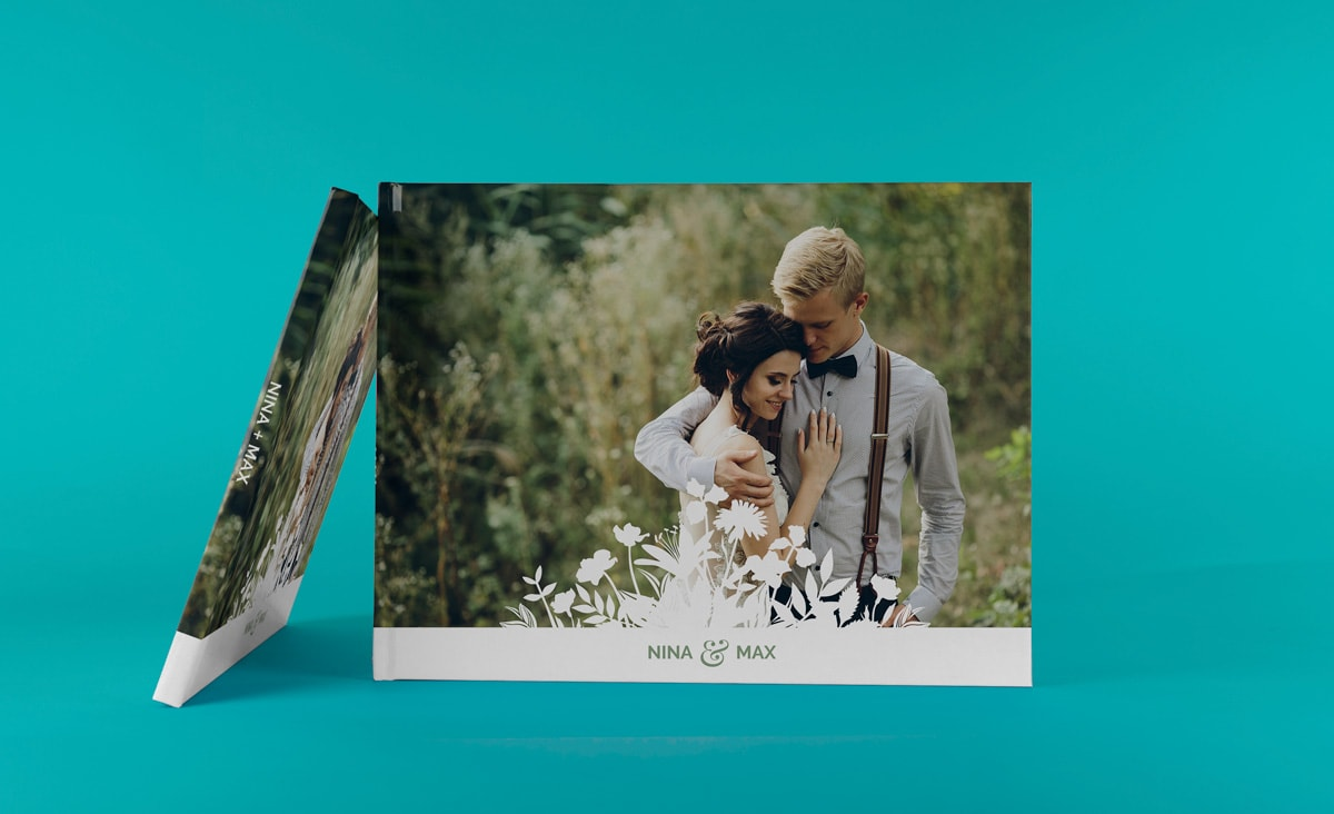 A wedding album with a photo cover against a bright blue background.