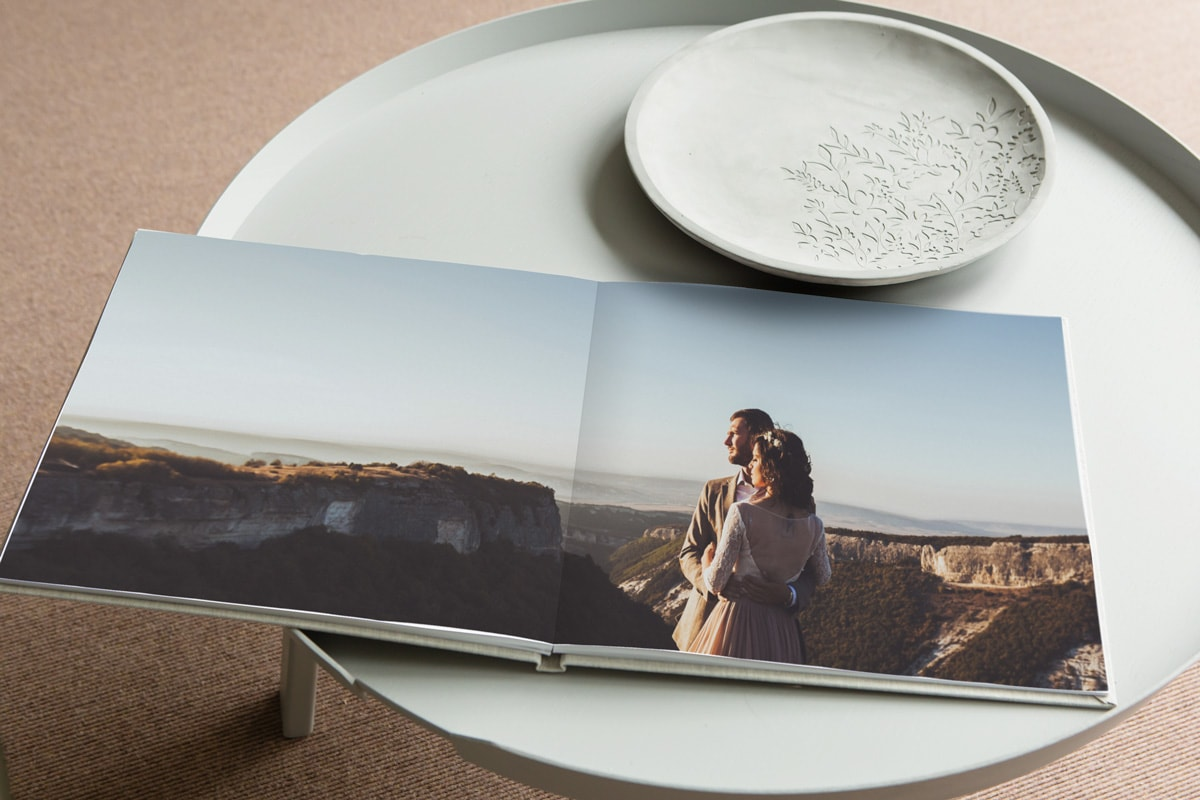 A wedding album open on a coffee table, with one wedding photo running across a double-page spread.