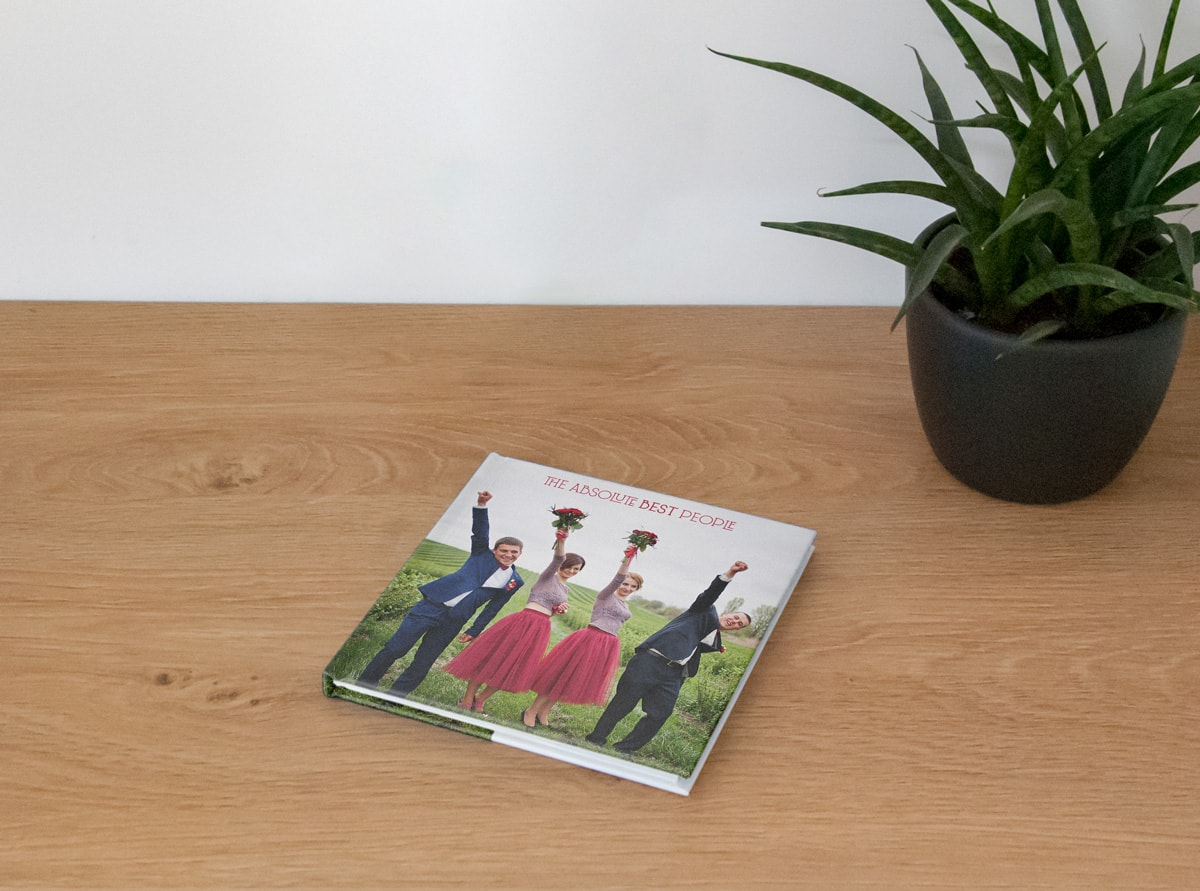 A small square wedding photo book on a wooden table top with bridesmaids and groomsmen on the cover.