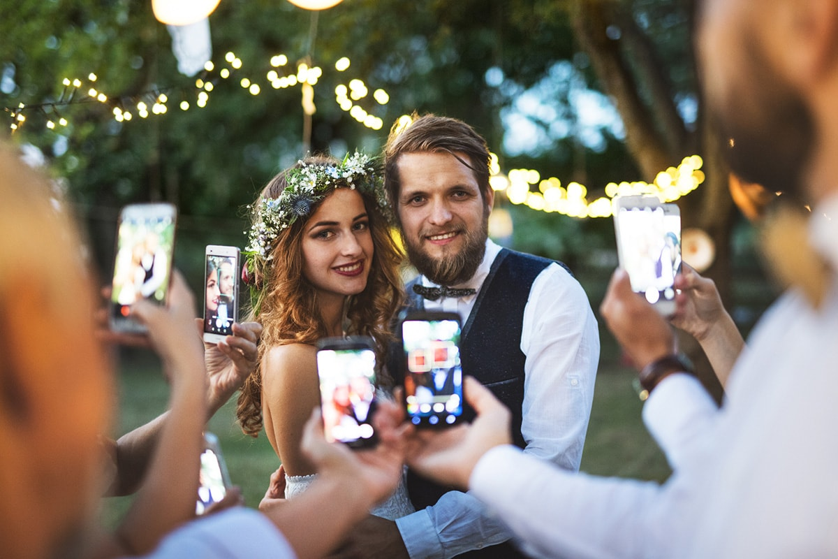 A picture of a bride and groom outside, with all the wedding guests taking pictures of them on their smartphones.