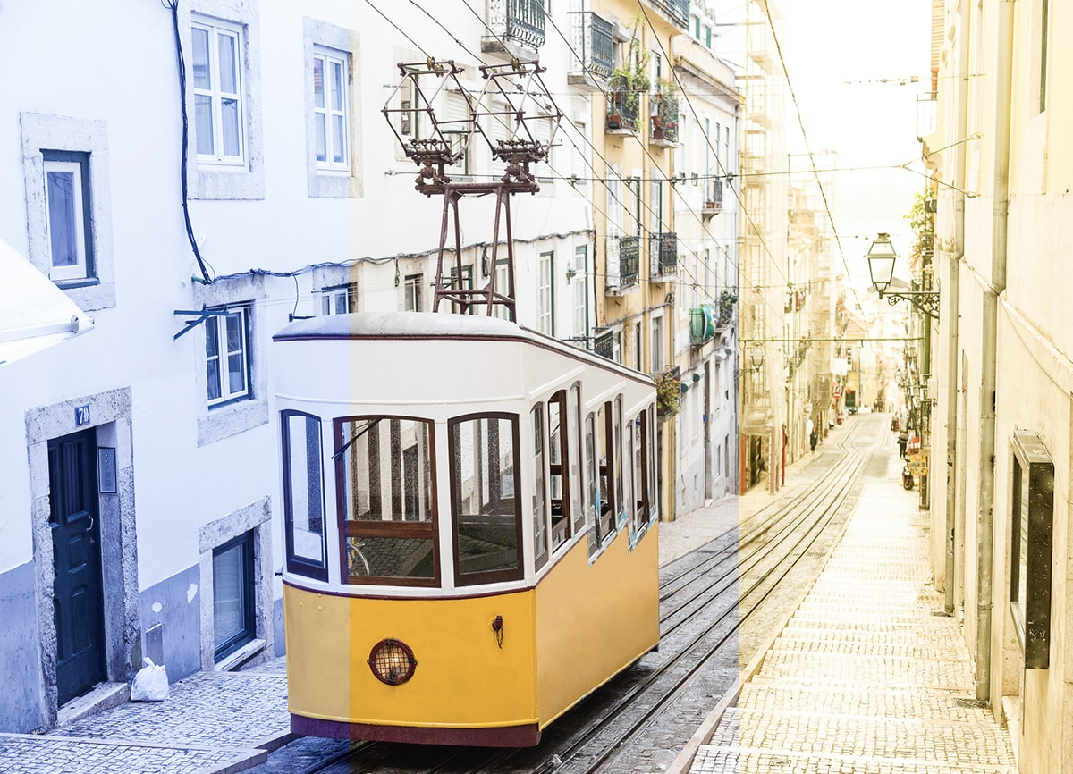 A photo of a tram going up a narrow street. The photo is split into three to show white balance; one third has blueish tones, the middle has balanced tones and the right-hand third has yellowish tones.