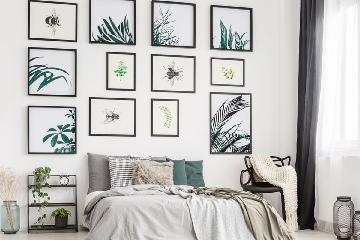 A bedroom with muted grey and green furnishings, white walls and a large collection of different-sized prints behind the bed, with illustrations of foliage and insects on.