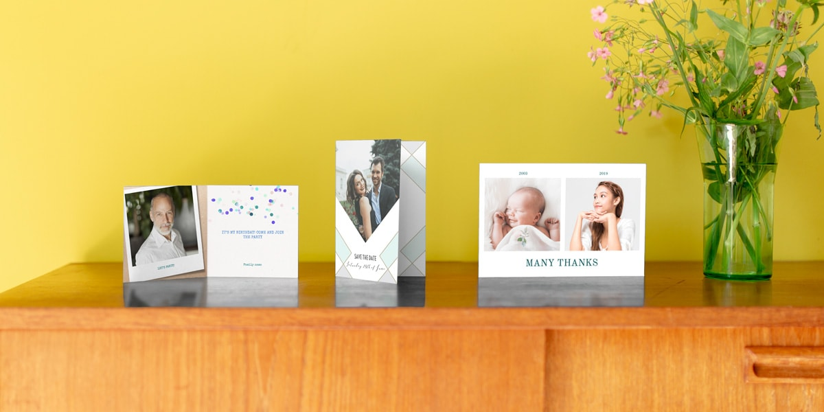 Three personalised photo cards on a wooden side table in front of a yellow wall