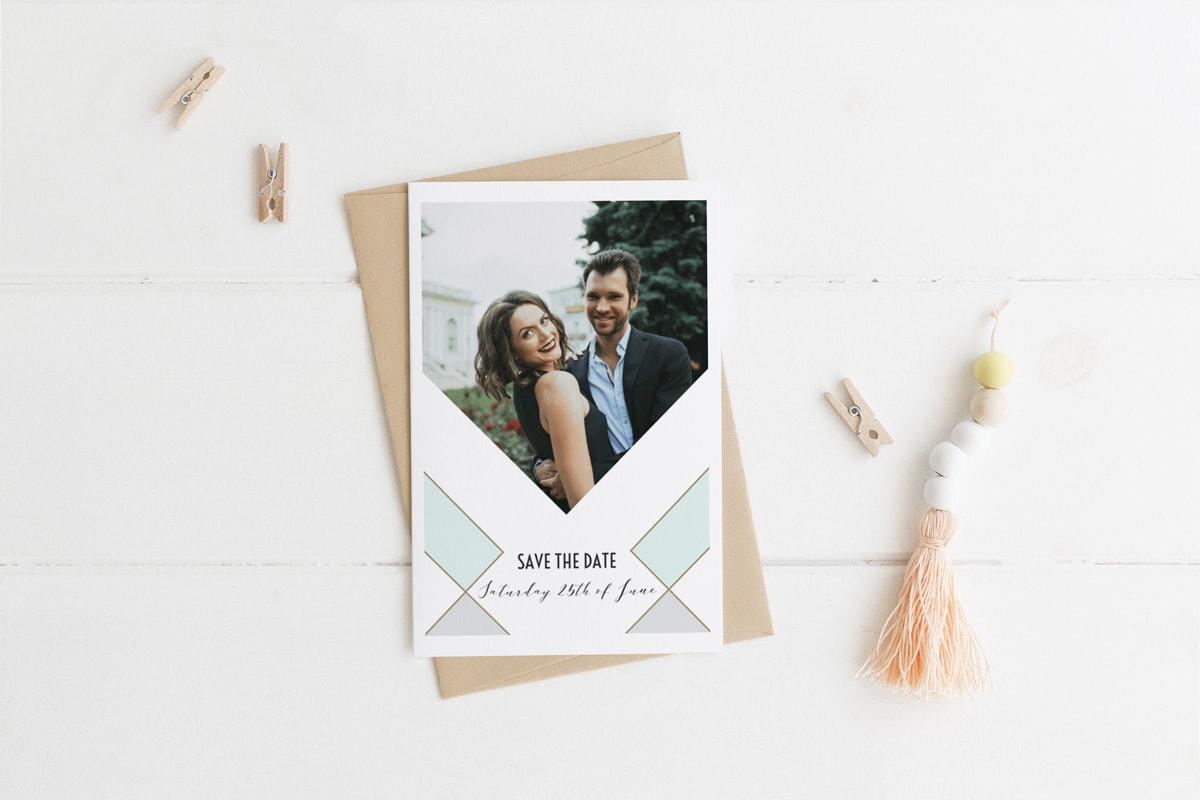 A personalised save the date wedding photo card against a white surface with small wooden pegs scattered around