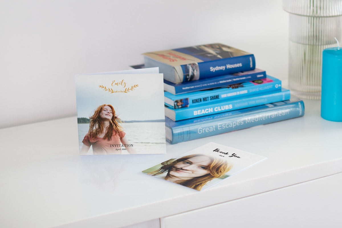 Two customised communion photo cards on a white table top with blue travel books in the background