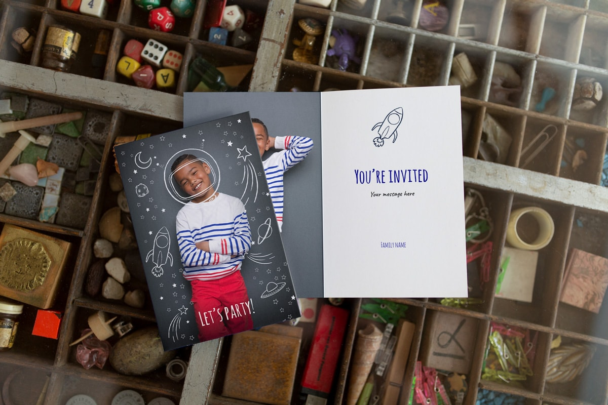 Two customised birthday photo cards, one with a photo of a boy on the front with astronaut and spaced-themed illustrations around him, the other is the same card design but open