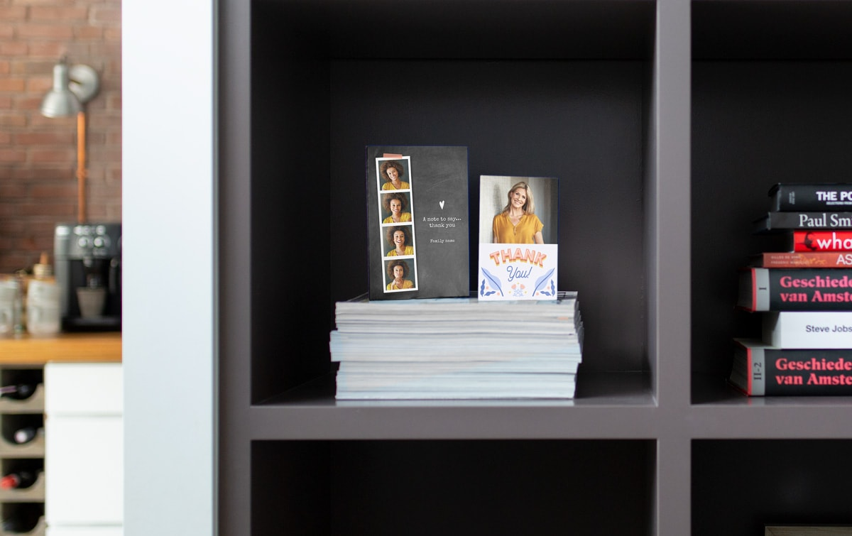 Dark grey shelves with two stacks of books and two customised photo thank you cards resting on top