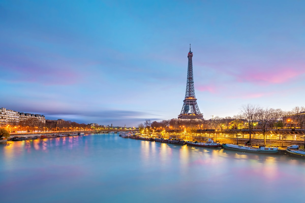 A photo of the Eiffel Tower taken across the river at dusk
