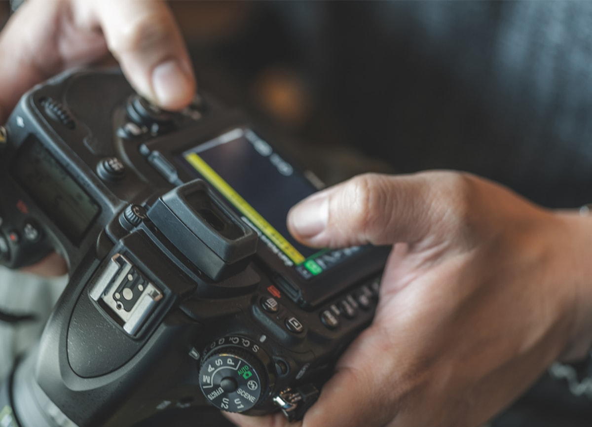 A close-up shot of someone adjusting the settings on their DSLR camera.