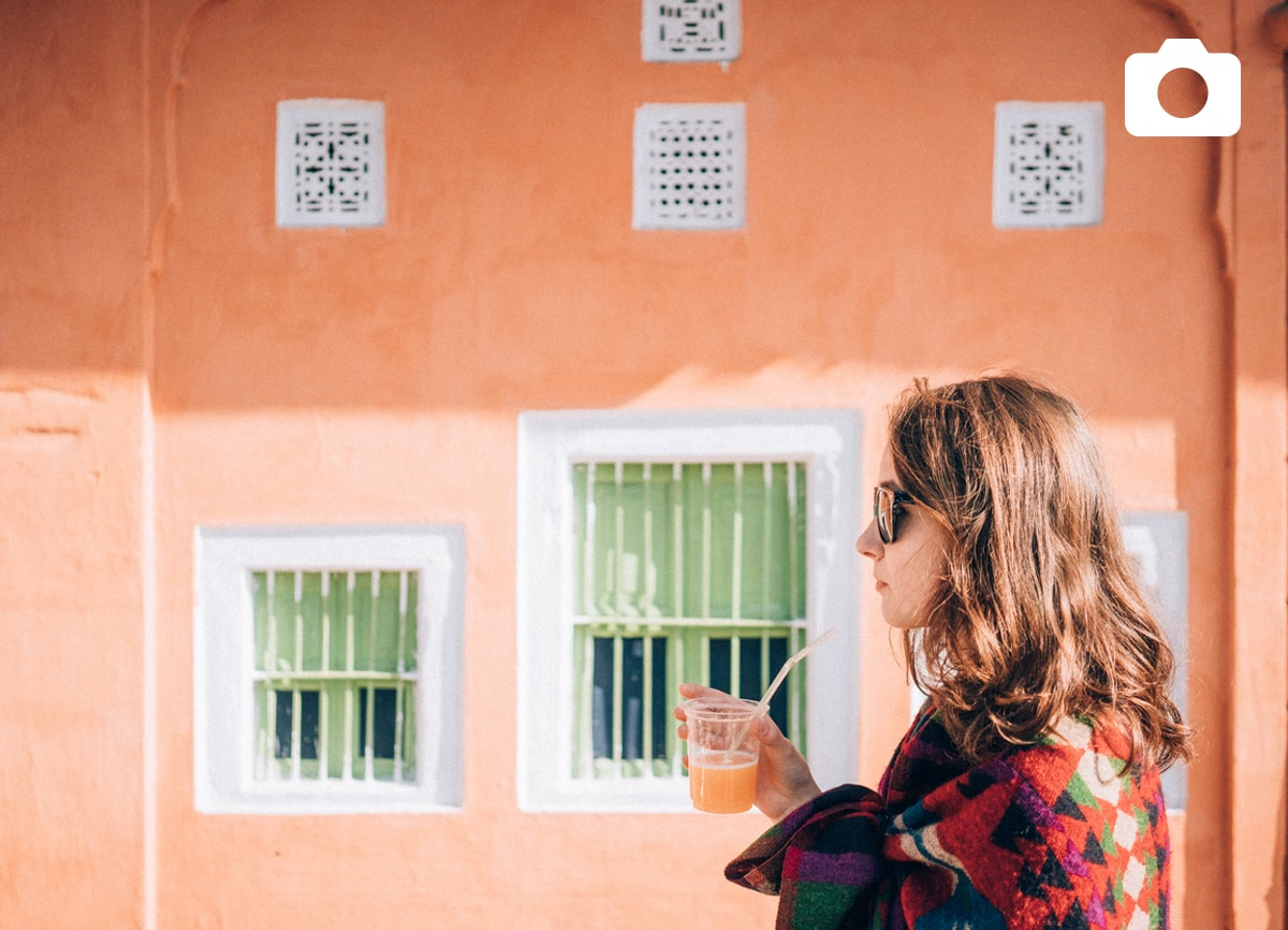A girl stood outside against a bright orange wall, drinking an orange juice.