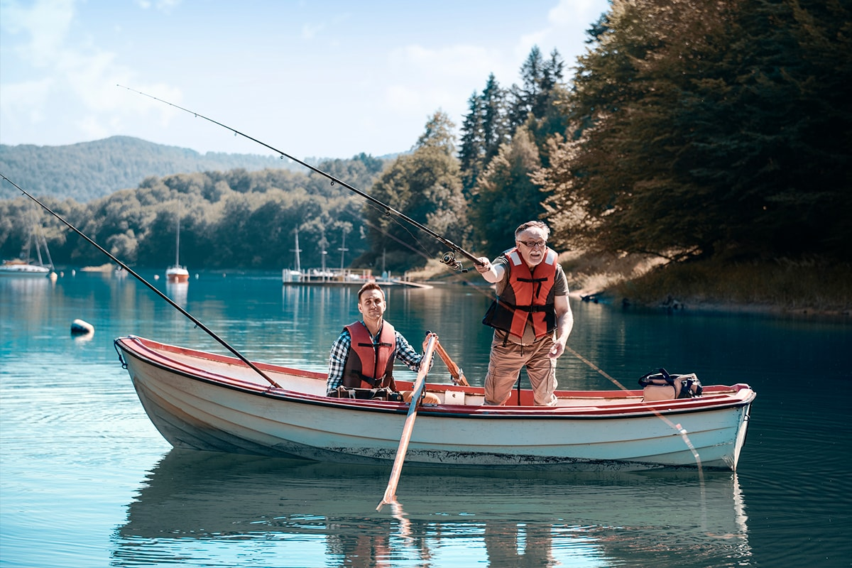 A photo of an older man and his son fishing in a boat on a lake.