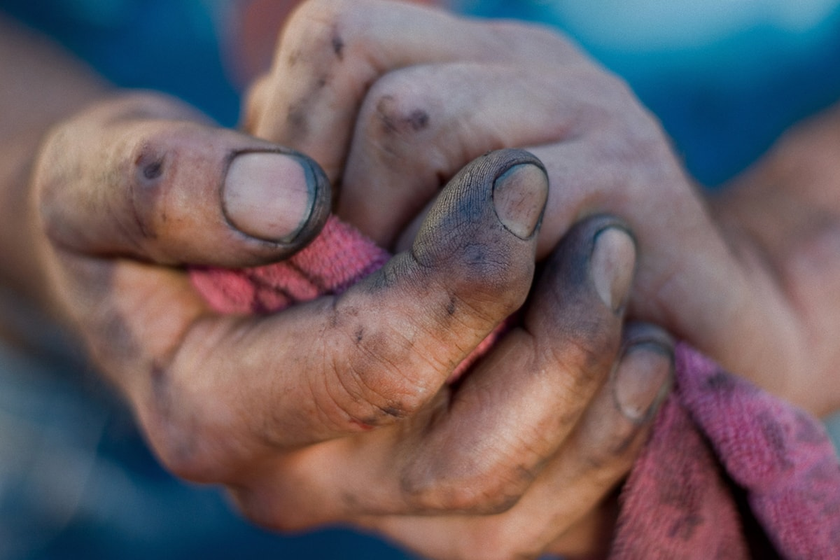 A close-up photo of a pair of man's hands, covered in soil, holding a cloth.