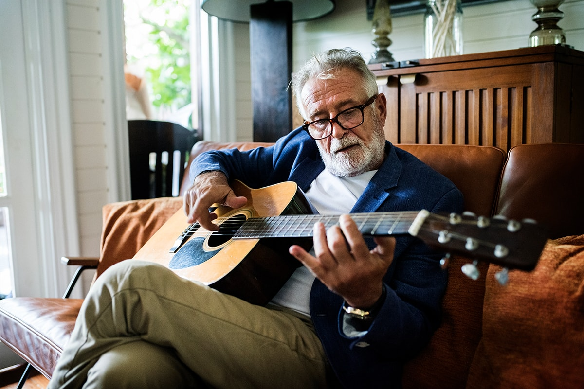 A photo of an older man, sat on a couch, playing an acoustic guitar.